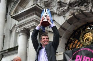 Gannon holds the League 2 Playoff trophy aloft outside Stockport Town Hall (image from manchestereveningnews.co,.uk)
